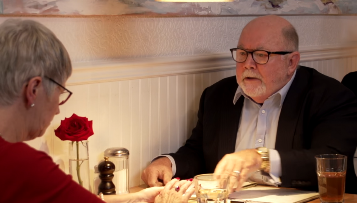 Screen capture of male and female arguing in a restaurant